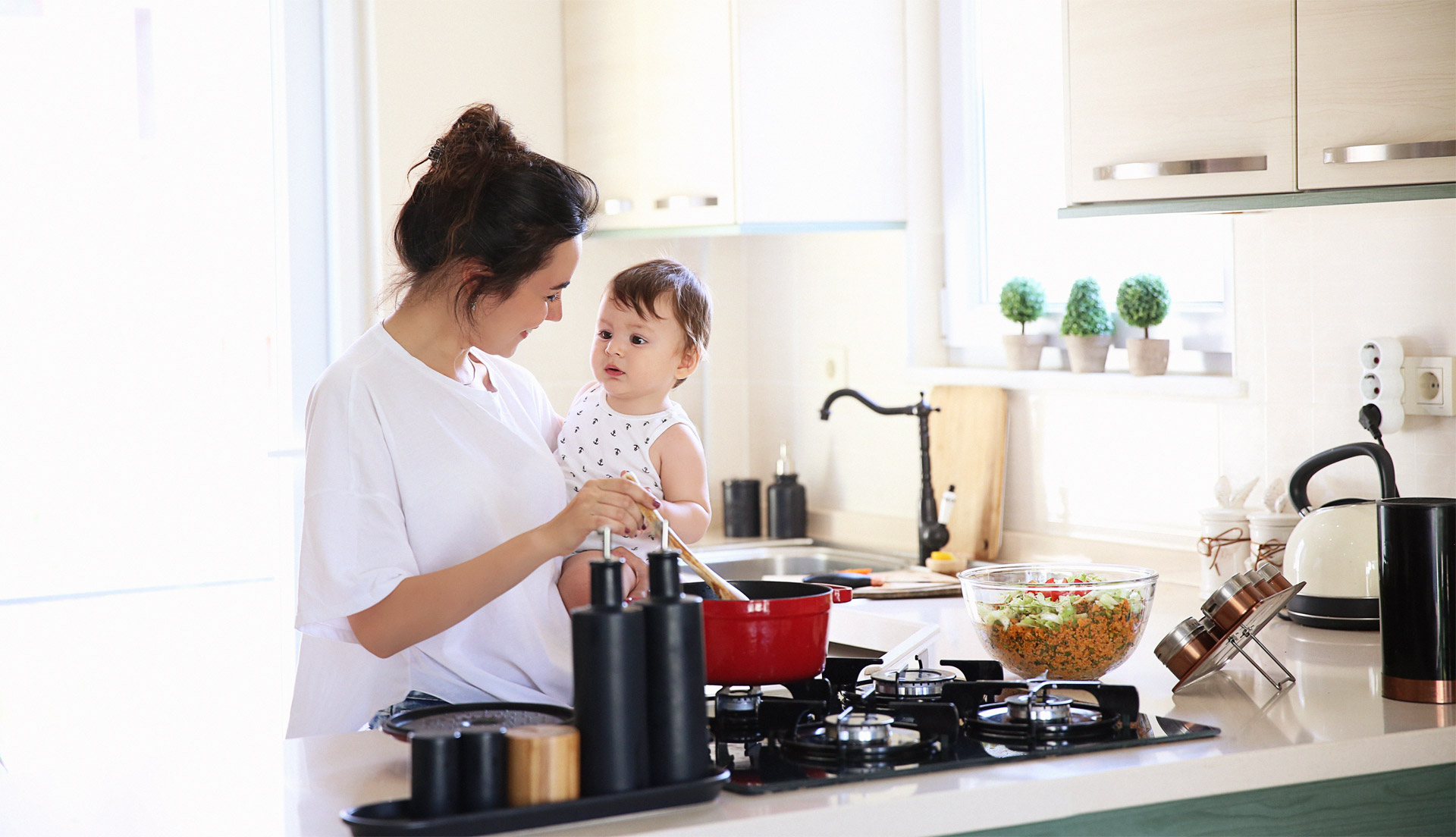 A mother holding a toddler and cooking food