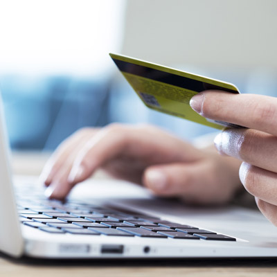 Image of one hand holding a credit card and another typing on a laptop