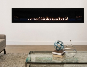 A long looking fireplace behind a glass coffee table